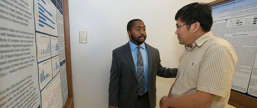 Malik McMullin explains his research to Dr. Steve Lim