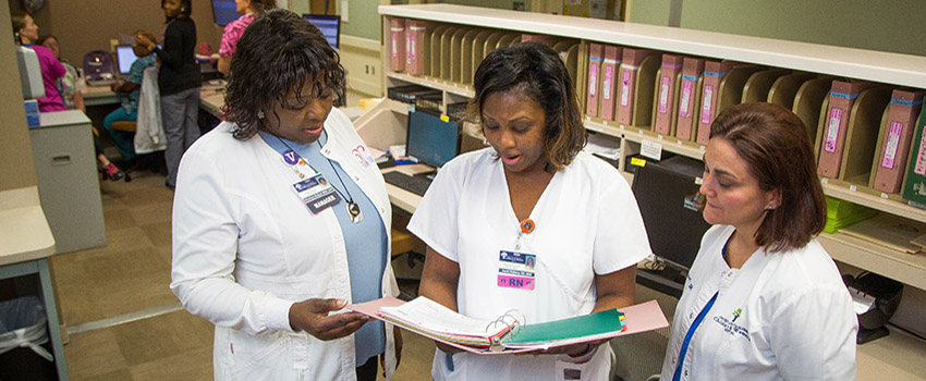 Three nurses in the Bachelors of Science in Nursing (BSN) Program reviewing a chart.