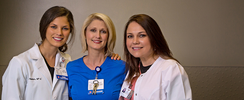 Three Doctor of Nursing Practice (DNP) nurses with their arms around each other in the Emergency Department