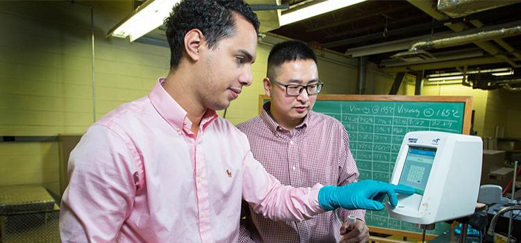 Omar Tahri and Assistant Professor Dr. Shenghua Wu working in the asphalt lab
