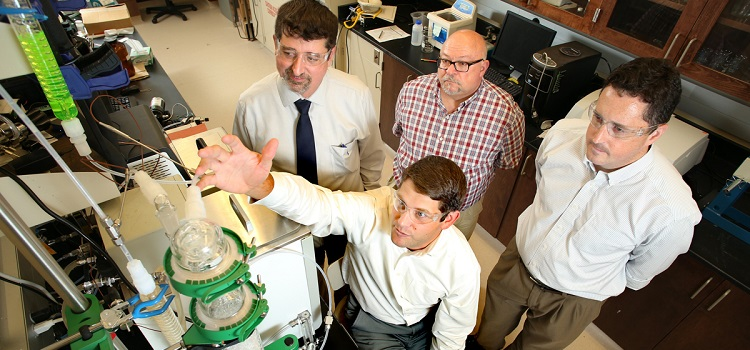Dr. T. Grant Glover, seated, demonstrates an early-stage prototype of the next-generation carbon dioxide scrubber being developed for the International Space Station. Colleagues Dr. Matthew Reichert, from left, standing, Dr. James Davis and Dr. Kevin West are colleagues on the research project, which is financed by a $1.1 million grant from NASA.