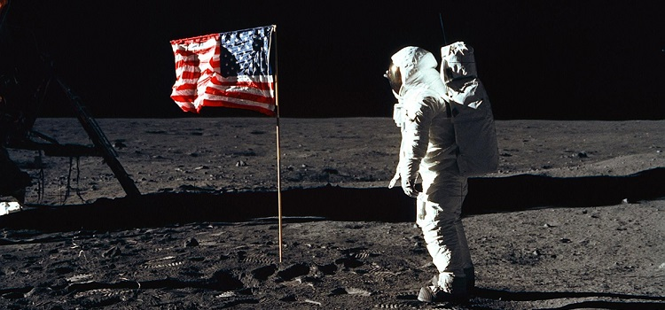 """Astronaut Edwin """"Buzz"""" E. Aldrin Jr., lunar module pilot of the first lunar landing mission, poses for a photograph beside the deployed United States flag. NASA photo."""