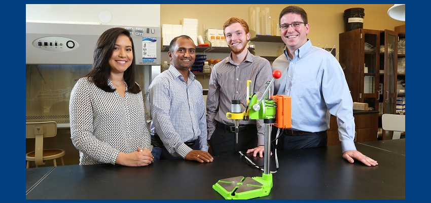 """Dr. Dhananjay Tambe, second from left, an assistant professor in mechanical engineering and pharmacology, worked with engineering students, from left, Cassandra Chapman, Brandon Stokley and Quentin Morris to develop the """"Tighten It"""" smart drill prototype. Chapman and Stokely graduated Saturday."""