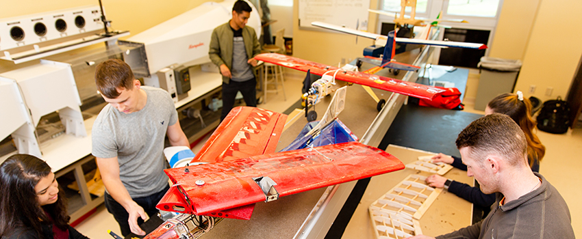 Mechanical Engineering students working on plane.