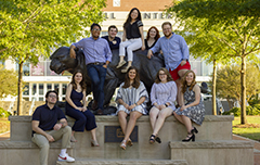 Honors Students sitting on Jaguar Statue in font of the Mitchell Center