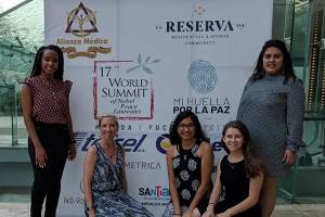 Students wth Dr. Cooke in front of world summit banner
