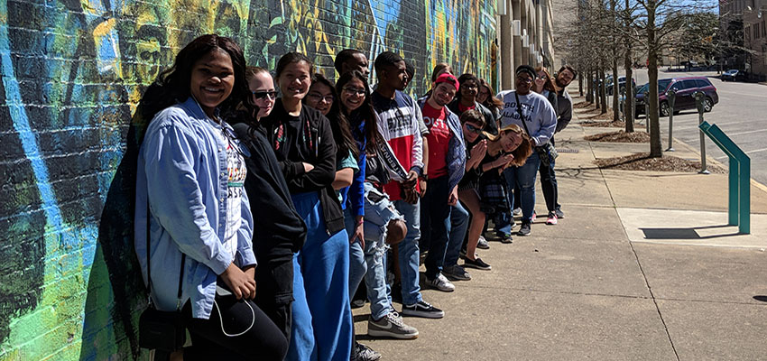 Group of Honors students standing beside grafitti covered wall on trip to Selma and Montgomery