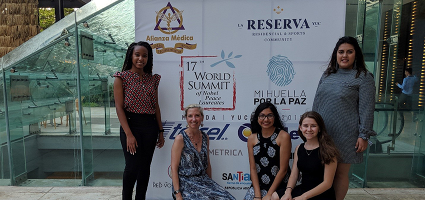 Dr. Cooke with students in front of banner at World summit.