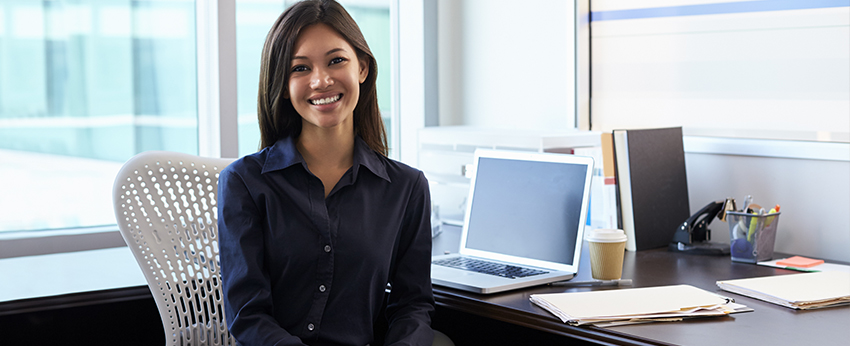 Girl smiling in front of desk