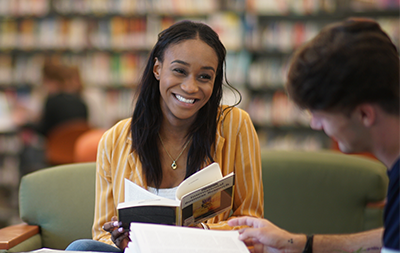 Female student holding a book smiling at a desk in the library
