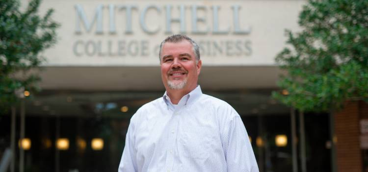 Dr. Chris Lawrey stands proudly outside the Mitchell College of Business. data-lightbox='featured'