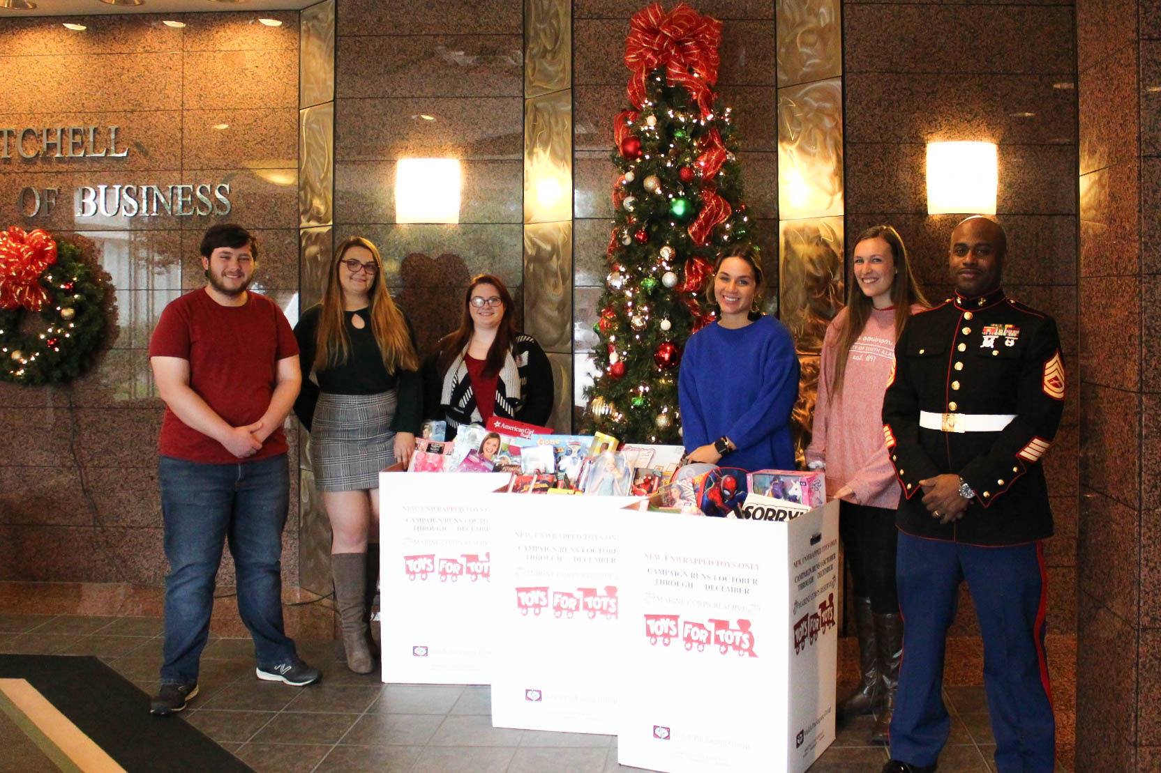 Students standing with toys collected for toys for tots.