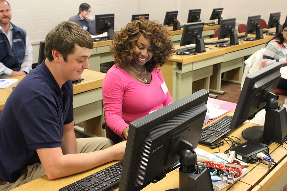 Students working in the tax assistance program at desks with computers.