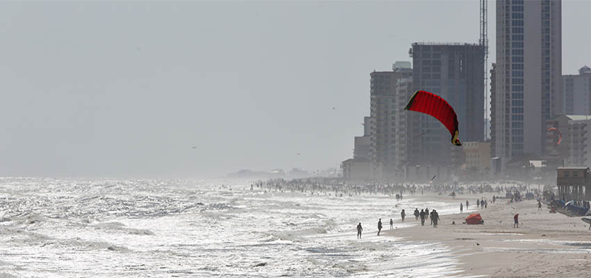 People walking on beach with condos