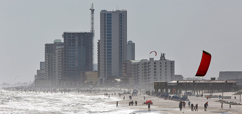 People walking on beach with condos in background.