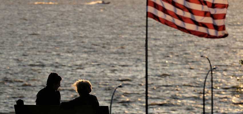 People looking at water with American flag waving.