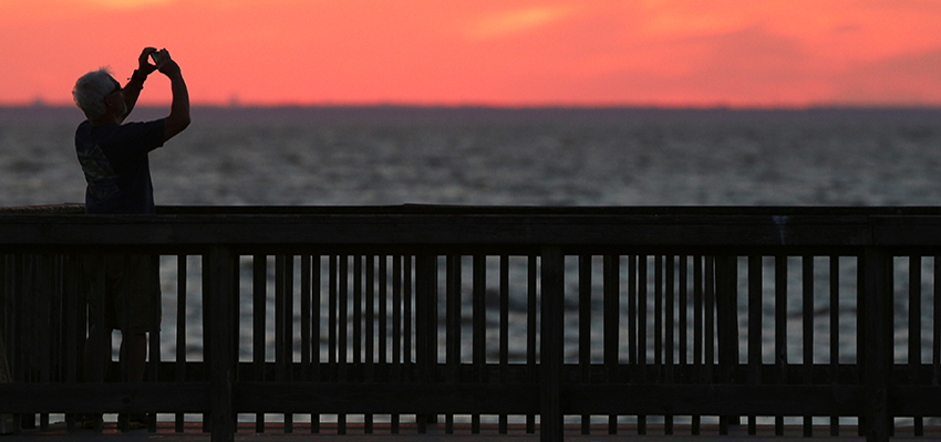 Man taking picture of sunset on pier