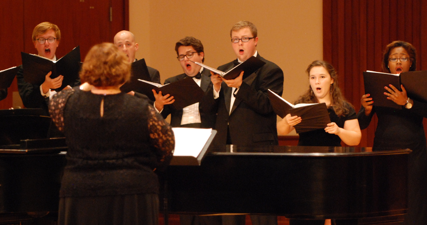 Six members of University Chorale with their director standing with music in hand as they perform on stage