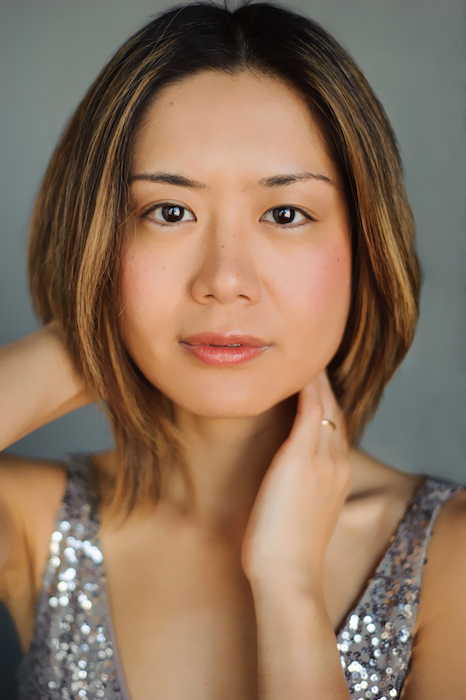 close-up of Jasmin Arakawa posed with one hand positioned on her neck and one behind her head