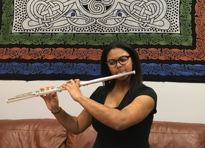 Nicole Carrion playing flute while standing in front of colorful tapestry