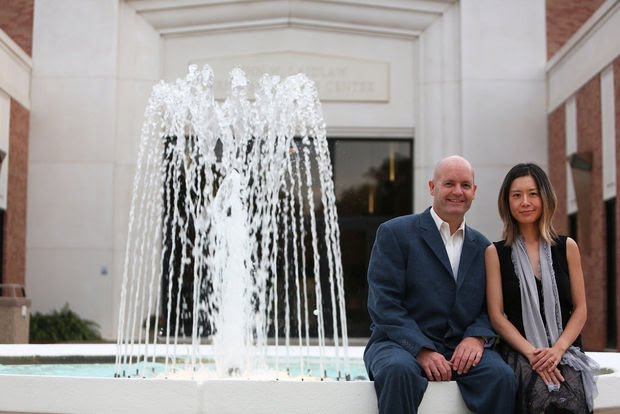 Rudolf Haken and Jasmin Arakawa seated beside fountain in front of Laidlaw Performing Arts