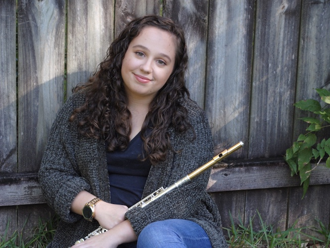 Pictured artistically in her back yard in front of a fence, holding her flute, is Hanna Ardrey. data-lightbox='featured'