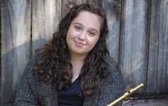 Pictured artistically in her back yard in front of a fence, holding her flute, is Hanna Ardrey.