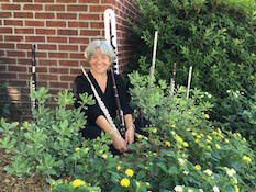 Dr. Andra Bohnet poses in a garden with artistically placed flutes around her.
