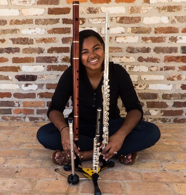 Nicole Carrion seated in front of brick wall with all her wind instruments