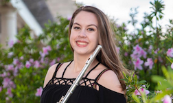 Dressed in performance attire, flutist Victoria French is pictured outdoors amongst plants on a patio.