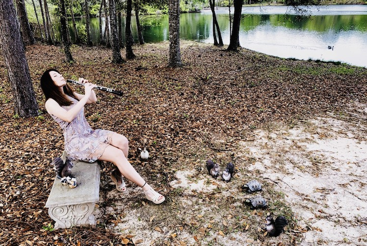 Oboist Tiffany Fresne pictured in a local park serenading various wild creatures, including the resident turtles.