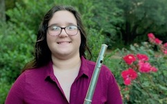 Pictured out-of-doors with flute in hand is Amanda Gooch.