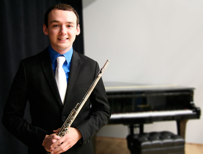 Travis Jones standing with flute in hand and piano in background