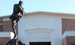 Pictured is the front entrance of the Laidlaw Performing Arts Center with the fountain and piper statue in the foreground.
