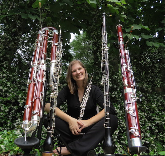 Rebecca Mindock seated near shrubs surrounded by large and small reed instruments