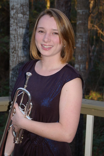 Paige Nelson with her trumpet in night shot with trees in the background