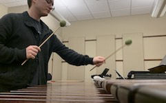 Pictured with mallets in hand playing the marimba is percussionist Kevin Newsome.
