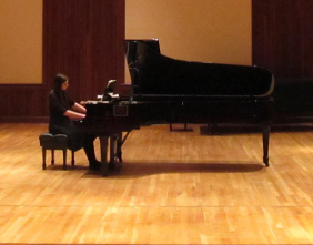 student seated at grand piano