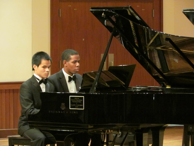 Wei Min Patrick and Joshua Vaughn seated and playing together at grand piano