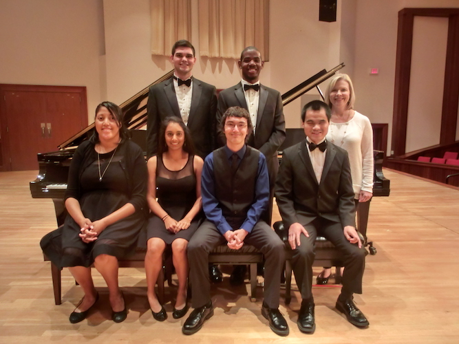 members of USA Piano Ensemble seated/standing near grand piano on stage