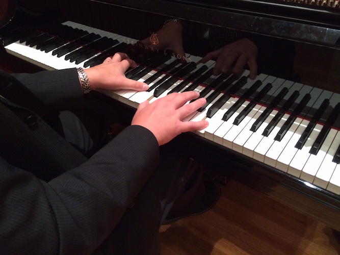 Pictured are the hands of pianist at the keyboard.
