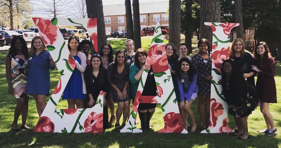sisters of Sigma Alpha Iota posed among the pine trees with giant floral print Sigma Alpha Iota letters