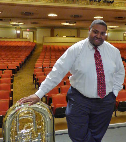 Matthew Selete with tuba standing in auditorium with red seats in the background