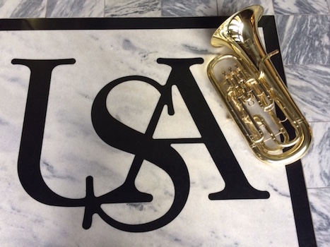 Euphonium laying beside USA logo on marble floor