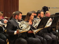 Members of the University Band are pictured on stage and in performance.