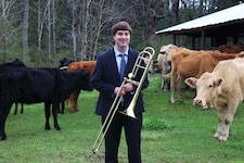 Pictured is trombonist Patrick Whitehurst standing artfully in a corral full of cows.  (This is not a mistaken caption!)