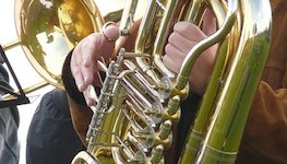 Pictured is a stock photo of a tubist showing only the valve section of the instrument and the hands of an anonymous performer.
