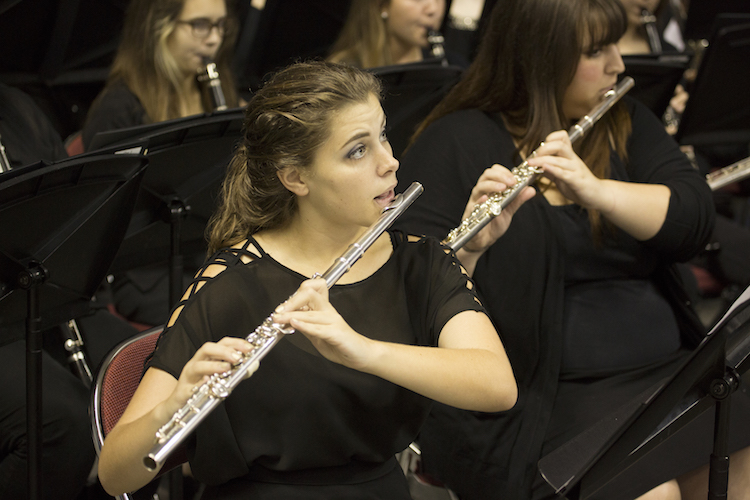 Pictured in performance is a flutist in the USA Wind Ensemble.