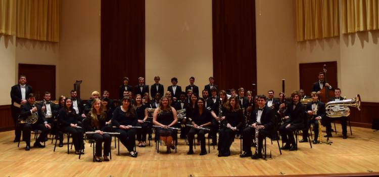 USA Wind Ensemble posing on stage