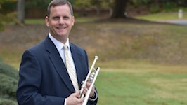 Pictured outside the Laidlaw Performing Arts Center holding one of his many trumpets is USA Faculty Dr. Peter Wood.